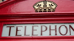 A red telephone booth found on the streetside in London Stock Footage