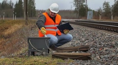 Railway employee with adjustable wrench near railway Stock Footage