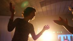 Cheerfully dancing jumping hands in air female fans at the concert Stock Footage