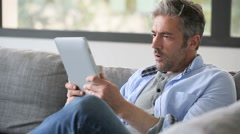 Mature man websurfing on internet with tablet - stock footage