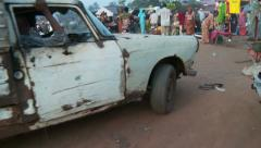 Rusty old car at Nigerian market Stock Footage