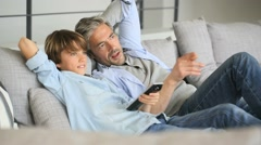 Stock Video Footage of Father and son watching tv relaxed in sofa