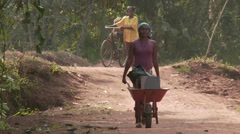 Woman pushing wheel barrow on jungle road - stock footage