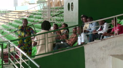 Nigerians singing in stadium grandstand - stock footage
