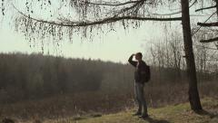 Tourist,glade,Guy examines all around,man standing in a glade,talking on mobile Stock Footage