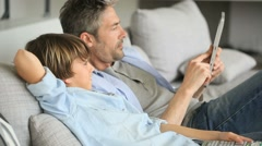 Father and son choosing tv program on tablet - stock footage