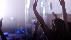 Cheerfully dancing jumping hands clap in air female fans at the concert - stock footage