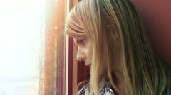 Hopeless young woman lost in her thoughts: sad woman looks out her window Stock Footage