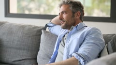 Mature man sitting in sofa and answering the phone - stock footage