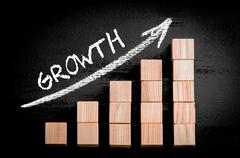 Word Growth on ascending arrow above bar graph of Wooden small cubes isolated - stock photo