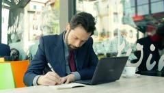 Businessman working outdoor sitting in a cafè: using laptop, notepad and pen Stock Footage