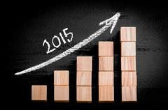Year 2015 on ascending arrow above bar graph of Wooden small cubes isolated o - stock photo