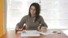 Businesswoman with financials problems: checking the balance sheets: calculator Stock Footage
