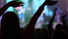 Audience swaying and clapping hands in flashing spotlights on a concert - stock footage