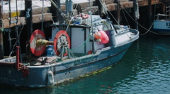A SMALL FISHING VESSEL SITS AT THE DOCK - stock footage