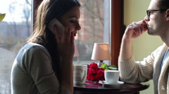Couple drinking coffee in the cafe and woman talking on cellphone Stock Footage