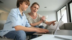 Mother looking after son doing homework on laptop Stock Footage
