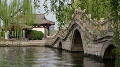 Green willow, arch bridge and pavilion Stock Footage