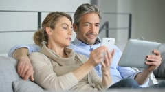 Mature couple at home using tablet and smartphone - stock footage