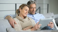 Mature couple relaxing in sofa and using digital tablet Stock Footage