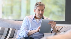 Mature man in sofa websurfing on digital tablet - stock footage