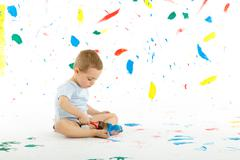 Adorable 3 year old boy child creatively stains on the wall. Stock Photos
