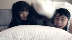 Little Asian child play hide and seek on the sofa bed Stock Footage