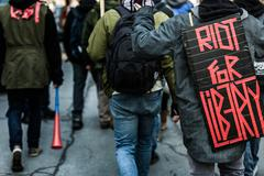 "Stock Photo of Closeup of the Back of a protester Wearing a Sign Saying ""Riot For Liberty""."