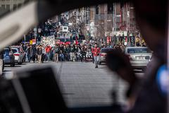 View of the First line of Protesters walking in the Street Through a Police Car  - stock photo