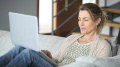 Woman sitting in sofa websurfing on internet with laptop - stock footage