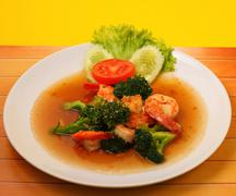 Shrimp and broccoli stir fry in sauce with a yellow background on a wood table Stock Photos