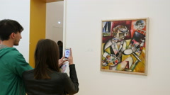 Woman taking picture of Chagall painting Stock Footage
