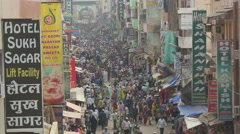 Crowds of people walk through busy bazaar past restaurants and shops in India Stock Footage