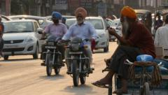 India, Amritsar, rickshaw rider waits for passengers on busy road Stock Footage