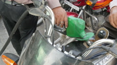 India, pumping fuel into a motorbike at a petrol station Stock Footage