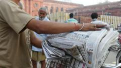 Sorting newspapers in the streets of Amritsar, India Stock Footage