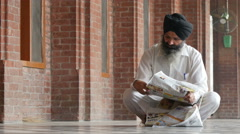 Religious Sikh man reads newspaper inside Golden Temple in Amritsar India Stock Footage