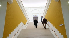 People walking up white staircase at museum - stock footage