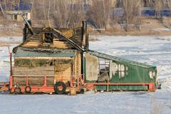 Burnt wooden structure standing on ice of river Stock Photos