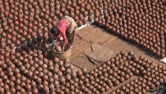 Bhaktapur, Nepal, Potters' Square, woman lays pots to dry, beautiful pattern Stock Footage