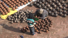 Nepal, Bhaktapur, Potters' Square, two boys help washing pots Stock Footage