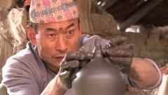 Nepal, Bhaktapur, potter makes a ceramic vase on a spinning wheel Stock Footage