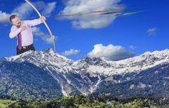 Businessman practicing archery with mountain valley in foreground - stock photo