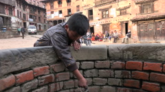 Nepal, Bhaktapur, a boy tries to take water from a well Stock Footage