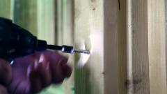 Screwing a screw into wood with a power drill Stock Footage