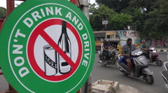 India, traffic drives past road sign, warning, drink and drive, alcohol Stock Footage