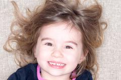 Headshot of young girl lying on a carpet Stock Photos