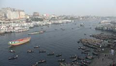 Cargo vessels, wooden rowing boats, ferry ships use busy river in central Dhaka Stock Footage