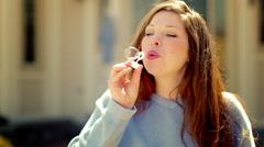 Slow motion woman blowing bubbles in warm sunshine HD Stock Footage