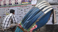 A rickshaw rider reads newspapers on a wall in Dhaka Bangladesh Stock Footage